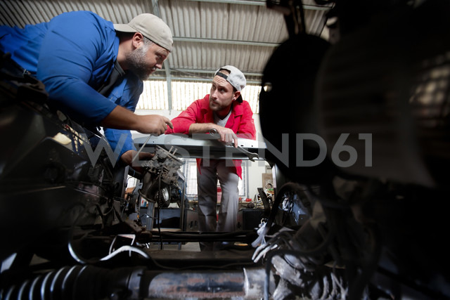 Mechanics repairing car in workshop - ZEF13801