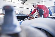 Mechanics restoring vintage cars in workshop - ZEF13804