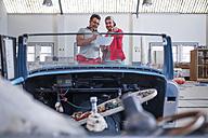 Mechanics restoring vintage cars in workshop - ZEF13810