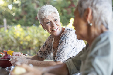 Portrait of smiling senior woman listening to her friend on terrace while preparing lunch - ZEF13837