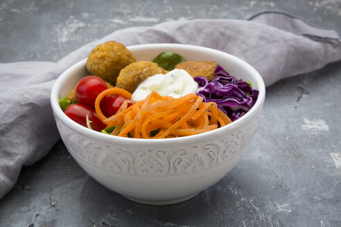 Lunch bowl of leaf salad, red cabbage, tomatoes, carrots, Falafel and yoghurt sauce - LVF06143