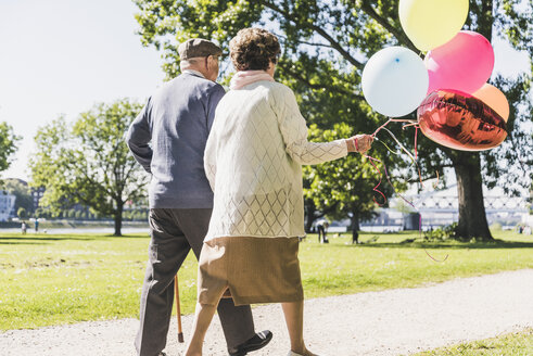Back view of senior couple with balloons strolling in a park - UUF10645