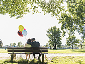 Happy senior couple with balloons sitting on bench in a park - UUF10648