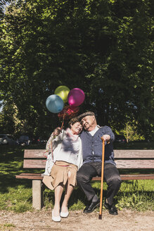 Happy senior couple with balloons sitting on bench in a park - UUF10651