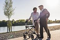 Happy senior couple strolling near river - UUF10660