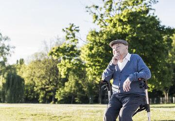 Pensive senior man sitting on his wheeled walker in nature - UUF10669