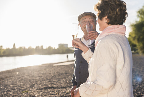Senior couple toasting with sparkling wine at sunset - UUF10672