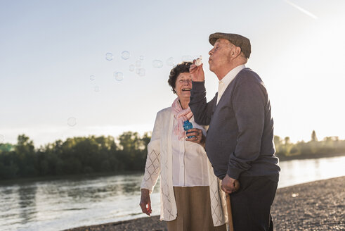 Senior man blowing soap bubbles on the beach at sunset - UUF10675