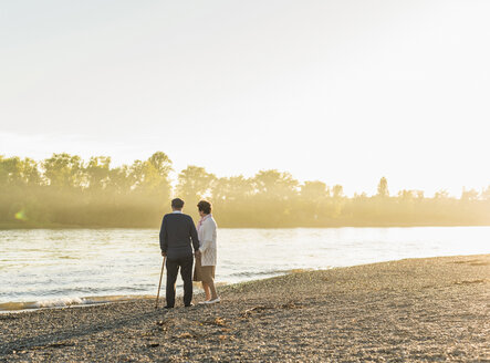 Senior couple standing on at riverside by sunset - UUF10681