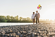 Senior couple with balloons strolling at riverside - UUF10684
