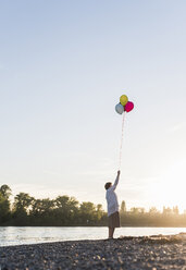 Senior woman with balloons on the beach by sunset - UUF10687