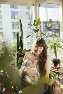Mother holding her newborn baby boy at home - MFF03571