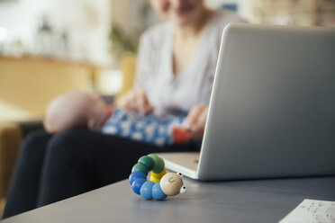Baby toy next to laptop of mother holding her newborn baby at home - MFF03580