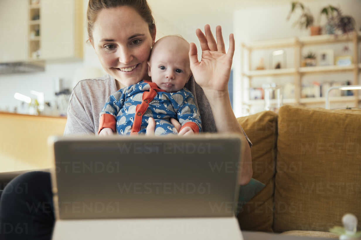 Mother and newborn baby taking a video call at home - MFF03586 - Mareen Fischinger/Westend61