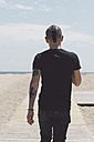 Back view of young man with mohawk haircut and tattoos walking on boardwalk to the beach - SKCF00303