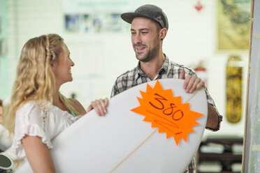 Shop assistant showing client surfboard prices - ZEF13847