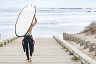 Woman walking to beach with surfboard - ZEF13853