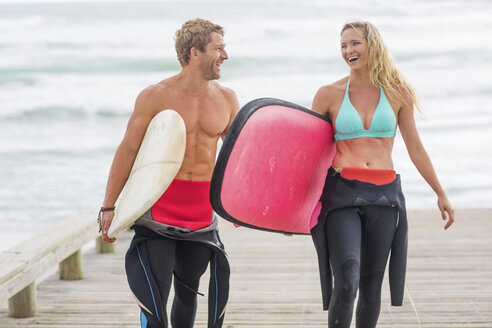 Couple walking from beach with surfboards - ZEF13856
