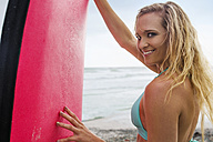 Smiling woman on beach with surfboard - ZEF13859