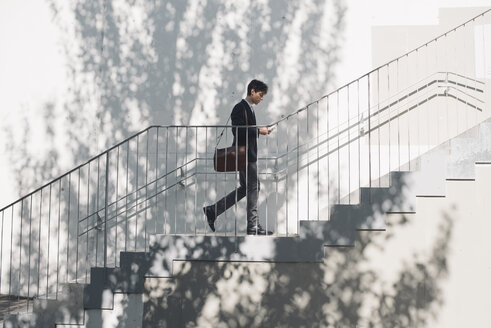 Young man in suit walking on stairs and looking at cell phone - SKCF00306