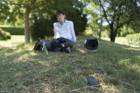 Young man sitting on meadow in park with cell phone away from him - SKCF00309