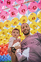South Korea, Gyeongju, father with a baby girl under colorful paper lanterns at Bulguksa Temple - GEMF01646