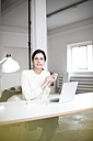 Portrait of businesswoman using laptop at table - JOSF00959