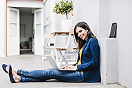 Smiling businesswoman using laptop on the floor - JOSF00962