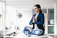 Businesswoman sitting on table meditating - JOSF00971