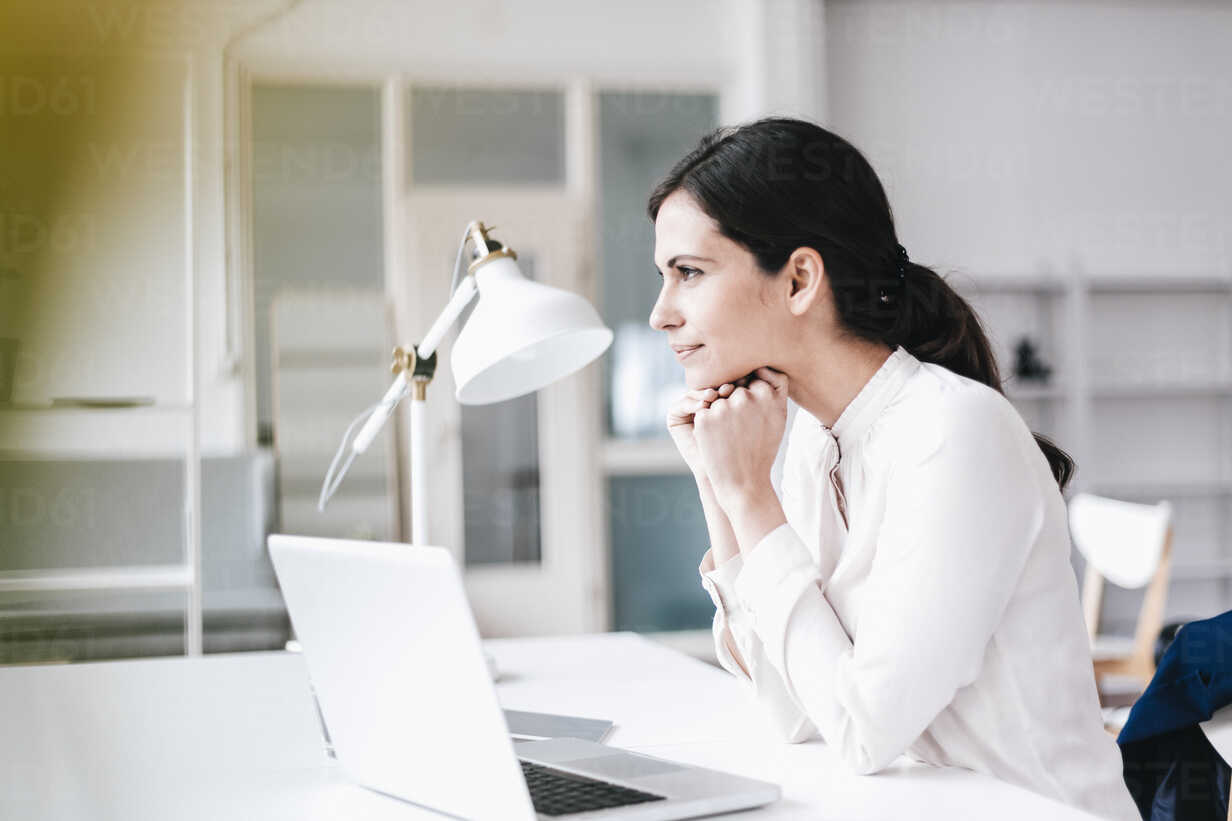 Businesswoman with laptop at table thinking - JOSF00974 - Joseffson/Westend61