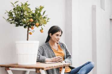 Woman relaxing next to orange tree - JOSF00980