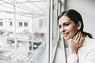 Smiling woman looking out of window - JOSF00986