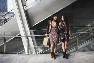 Two young women with shopping bags and cell phone in the city - MRAF00180