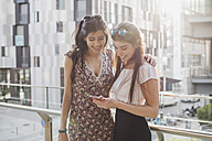 Two smiling young women looking at cell phone in the city - MRAF00186