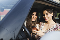 Two happy young women looking at cell phone in a car - MRAF00192