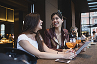 Two happy young women in a bar - MRAF00207