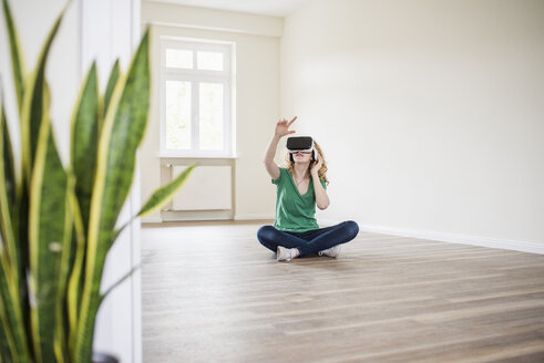 Woman in empty apartment wearing VR glasses - UUF10696