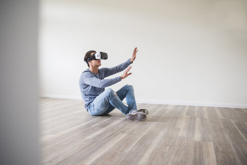 Man in empty apartment wearing VR glasses - UUF10699