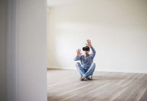 Man in empty apartment wearing VR glasses - UUF10702