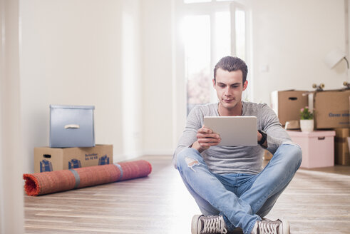 Young man in new home sitting on floor with tablet - UUF10705