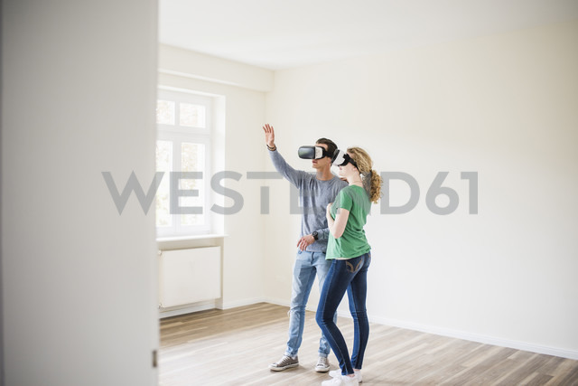 Young couple in empty apartment wearing VR glasses - UUF10708