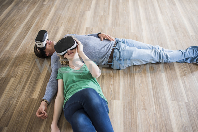Young couple lying on floor in empty apartment wearing VR glasses - UUF10711