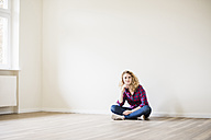 Young woman in new home sitting on floor - UUF10714