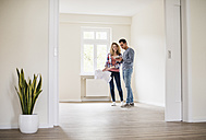 Young couple in new home with tablet and ground plan - UUF10720