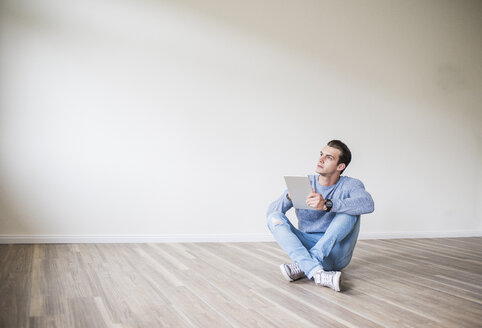 Young man in new home sitting on floor with tablet - UUF10723