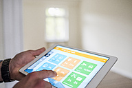 Man in new home using tablet with smart home apps - UUF10726