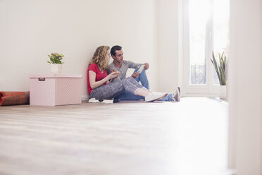 Young couple in new home sitting on floor with tablet - UUF10729