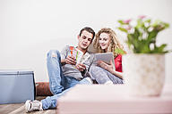 Young couple in new home sitting on floor with tablet choosing from color sample - UUF10732