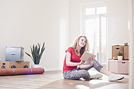 Young woman in new home sitting on floor with tablet - UUF10738