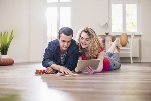 Young couple in new home lying on floor with tablet choosing from color sample - UUF10741